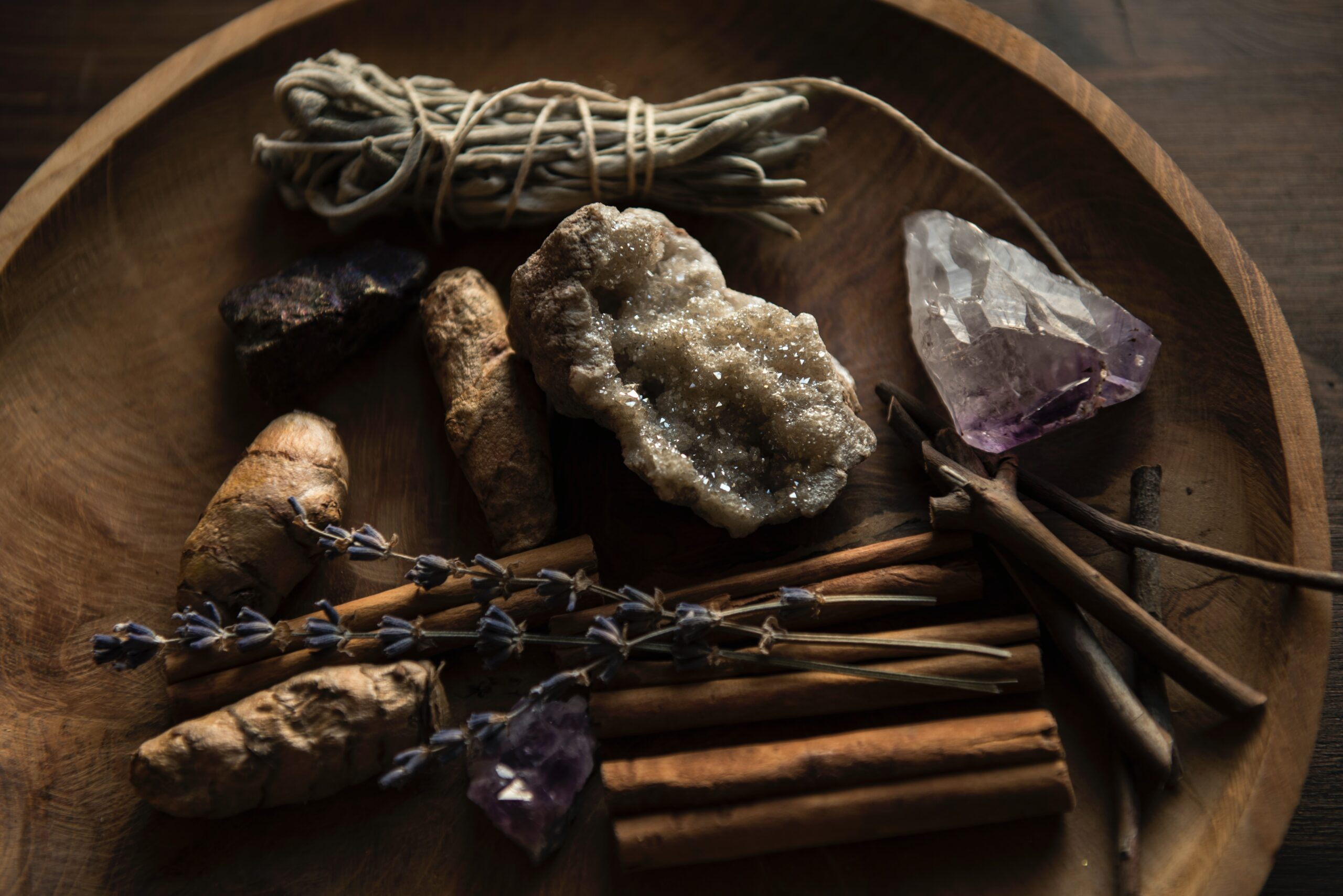 Wooden bowl with sage, lavender, cinnamon, and a crystal.