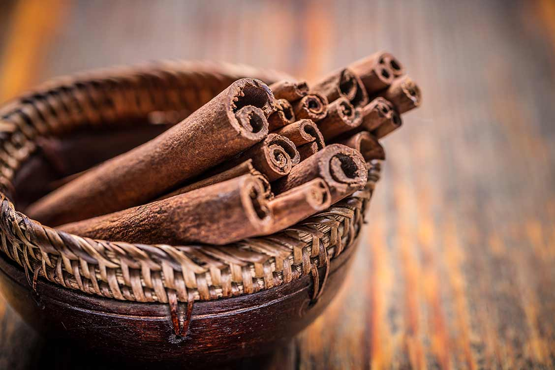 Basket full of cinnamon sticks on wooden table