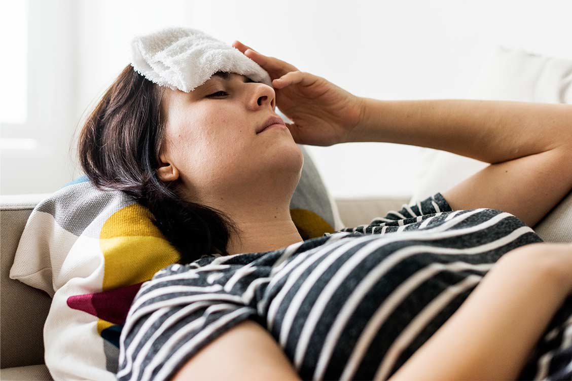 Woman with a cold and fever placing wet towel on her head