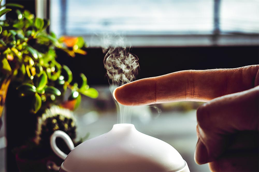 Person using aromatherapy blends in diffuser