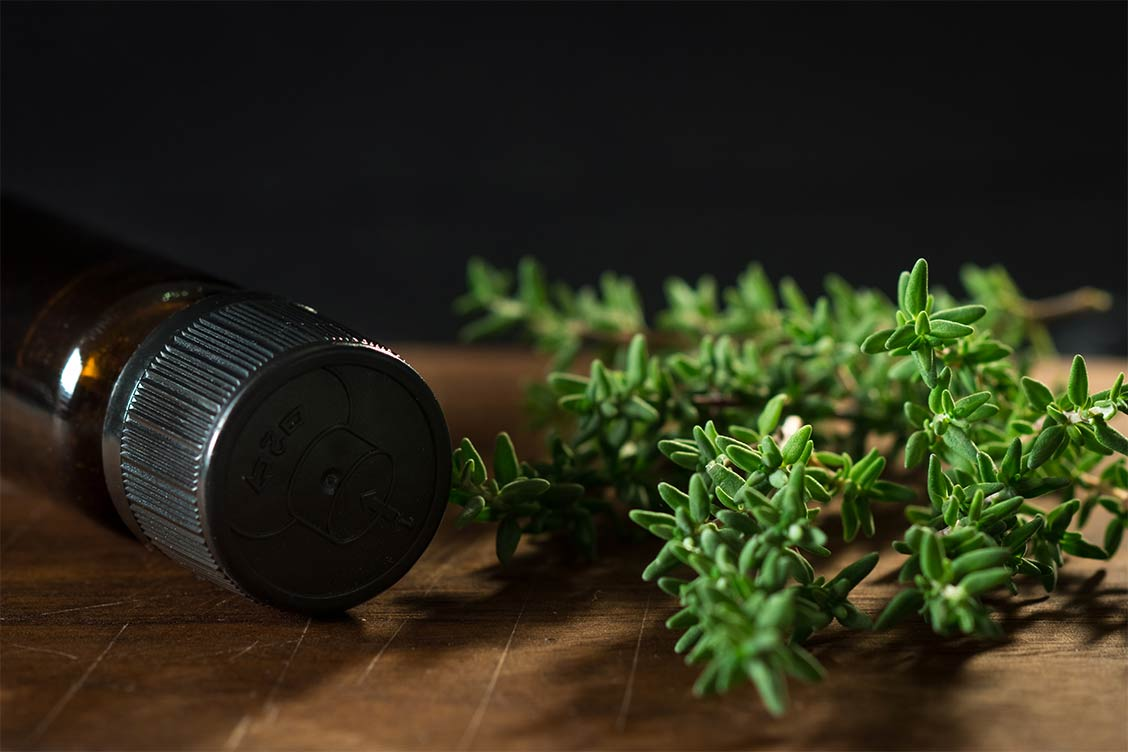 Essential oil container next to pile of Thyme