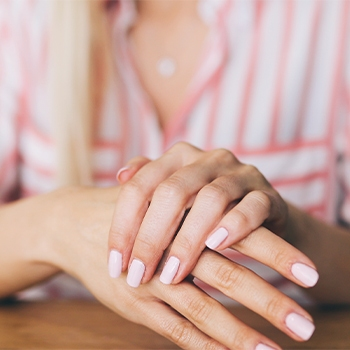 Woman applying body blend essential oils to hands